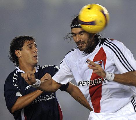 El uruguayo Abreu -acá ante Bianchi- fue el gran triunfador de la noche: marcó tres goles y se reencontró con la hinchada de la 'Banda' (Foto: EFE)