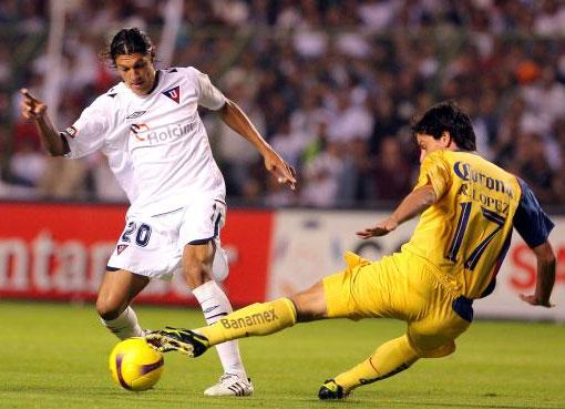 López se barre ante Vera, la figura del campo. LDU manejó bien el resultado (Foto: MEXSPORT)