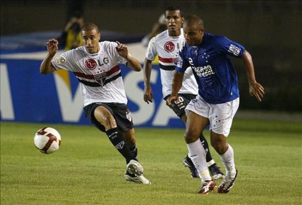 APRETADO NOMÁS. Jonathan disputa el balón con el paulista Jorge Wagner. Cruzeiro pegó primero en el duelo brasileño de los cuartos (Foto: EFE)