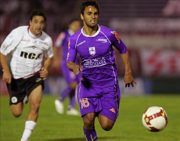 DEFENSAS BAJAS. Sebastián Ariosa corre al balón, pero no impedirá la caída en casa de Defensor Sporting a manos de Estudiantes de La Plata (Foto: EFE)