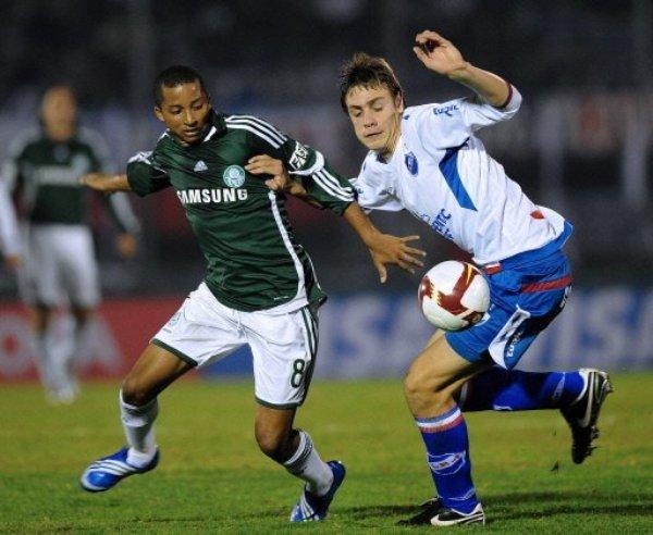 VERDE EMBOLSADO. Palmeiras no pudo en Montevideo y quedó fuera de la Copa a manos de Nacional. En la foto, Willians dos Santos pelea el balón con Matías Rodríguez (Foto: AFP)