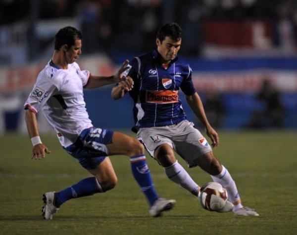 CRUCE DE TOCAYOS. Romero lleva el balón ante Ruiz Peralta. El Nacional más conocido, el de Montevideo, superó el trance inicial y cerró de óptima forma su periplo en primera fase (Foto: AFP)