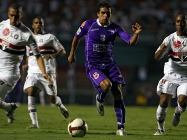 INTENTO DISPAR. Amado se abre paso él solo entre la zaga del Sao Paulo, que siempre fue más que Defensor Sporting (Foto: FIFA.com / AFP)