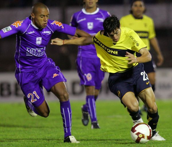 DE CERQUITA. Pablo Pintos persigue a 'Nico' Gaitán. Boca pasó muchos apuros ante los violetas de Defensor (Foto: EFE)