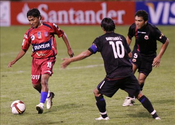A QUE NO ME LA QUITAS. Ronald Gallego, del Universitario de Sucre, controla el balón ante la atenta mirada de los ecuatorianos Luis Saritama y Edwin Tenorio (Foto: EFE)