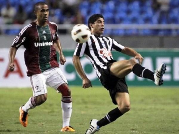 CON UNO NO BASTA. Julio César va a la marca del atacante paraguayo Rodolgo Gamarra. El jugador guaraní anotó el empate transitorio para Libertad. (Foto: AP)