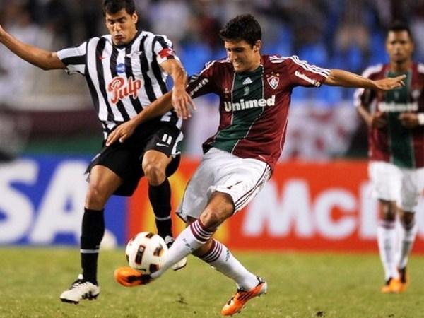PARA EL SEGUNDO. Marquinhos pelea el balón con el capitán de Libertad, Carlos Bonet. El brasileño le dio la ventaja a Fluminense tras el empate 'Gumarelo'. (Foto: AP)