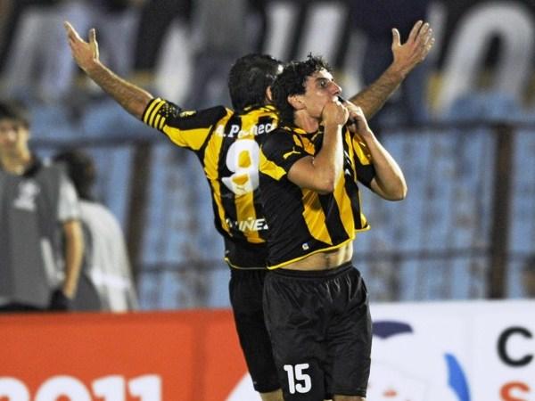LA GLORIOSA AURINEGRA. Matías Corujo y Antonio Pacheco celebran junto a la barra carbonera. Era el primero para el cuadro uruguayo. (Foto: AP)
