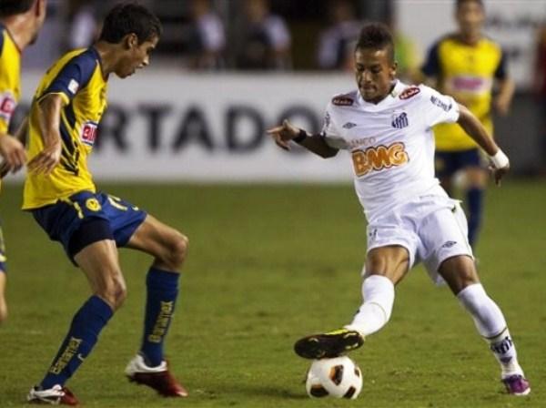SIGUE SIENDO EL REY. Neymar mostró todo su talento ante América de México. En la imagen, Diego Antonio Reyes sufre la gambeta del joven crack brasileño. (Foto: AP)
