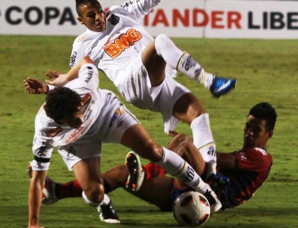 DOS SANTOS. El aguerrido cuadro paraguayo hizo sudar la gota gorda a los habilidosos atacantes de Santos. En la imagen, Elano y Neymar sufren la embestida de Julio Dos Santos. (Foto: Reuters)