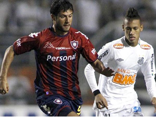 SIEMPRE AL ACECHO. Neymar atento a una lucha de balón ante Freddy Bareiro. El jugador brasileño fue el más desequilibrante de Santos. (Foto: EFE)