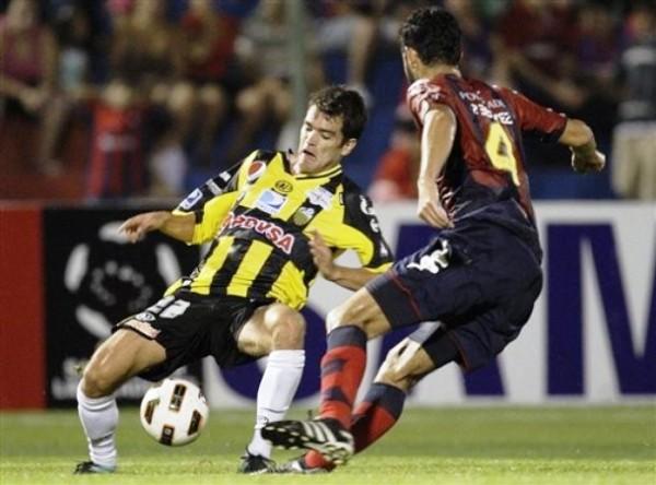 ¡QUÉ PATINADA! Sebastián Hernández no puede mantener el equilibrio ante la presencia de Benítez. Al igual que Hernández, Táchira sucumbió sin atenuantes ante Cerro Porteño y prácticamente le dijo adiós a la Copa. (Foto: AP)