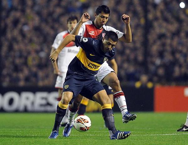 Juan Román Riquelme protege la pelota mientras Rinaldo Cruzado, muy activo durante el partido, se la intenta robar (Foto: AFP)
