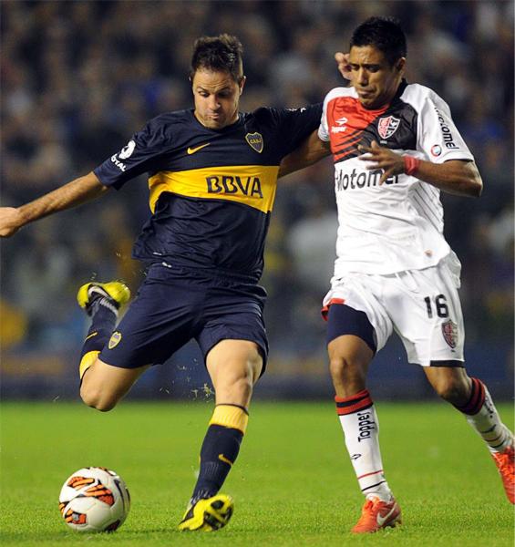 Boca intentó abrir rápido el marcador apelando casi a cualquier variante, tal como aquí que Juan Martínez ensaya un remate antes que Víctor Figueroa llegue al cruce (Foto: AP)