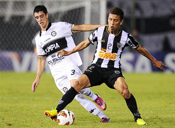 Además de anotar el primer gol de Olimpia, el uruguayo Alejandro Silva se dio maña para colaborar en la marca como aquí ante Marcos Rocha (Foto: AFP)