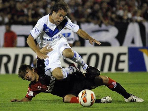 Gabriel Heinze se barre para interceptar el balón y de paso se lleva por delante a Federico Insúa, guía de la ofensiva de Vélez (Foto: EFE)