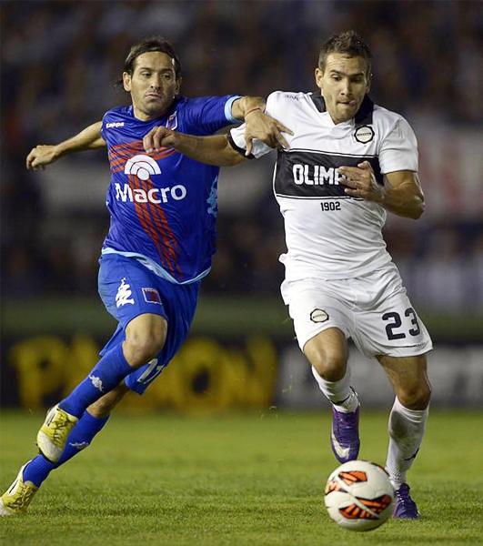 Ramiro Leone y Jorge Báez disputan el balón en el mediocampo, una de las muchas jugadas divididas durante el partido (Foto: AFP)