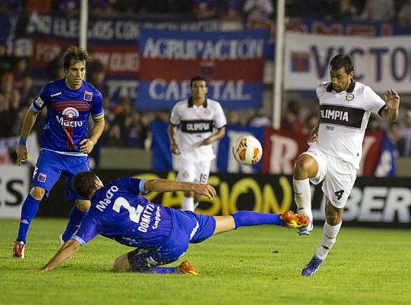 Alejandro Donatti pone el pie fuerte para robarle el esférico a Sebastián Ariosa de Olimpia (Foto: AFP)