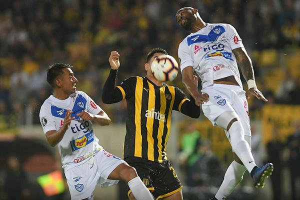 César Mena se eleva ante la presión de Gabriel Fernández. (Foto: AFP)