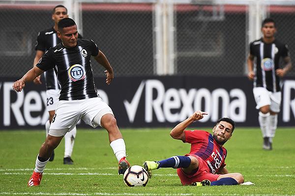 Castro sale con el balón dominado ante la barrida de Villasantti. (Foto: AFP)