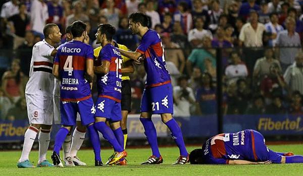 LA CALAMIDAD: Luis Fabiano ya lanzó la patada con la que buscó agredir a Alejandro Donatti que en el césped parece retorcerse de dolor. Al final ambos dejaron a sus equipos con uno menos (Foto: AP)