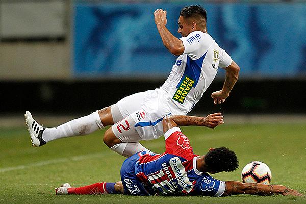 Maximiliano Bajter intenta salir con el balón mientras Douglas se barre. (Foto: Conmebol)