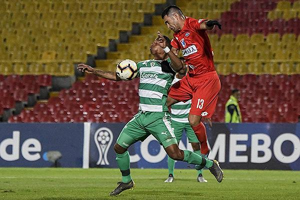 Peralta y Báez se enfrentan en la mitad de cancha por el balón. (Foto: AFP)