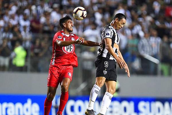 Oliveira se eleva y disputa el balón con Alvarado. (Foto: AFP)