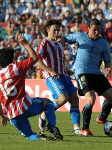 TODOS A LA MARCA. Para resistir los ataques uruguayos, todo el equipo paraguayo se unió en el control. Riveros va agresivo contra Rodríguez (Foto: FIFA)