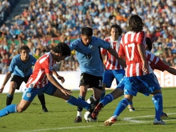 NO FUE TAREA FÁCIL. Pereira busca el remate, pero los paraguayos haran lo imposible por evitarlo. Uruguay ganó, pero le costó todo el partido (Foto: FIFA)