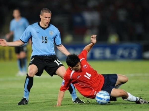 LEVANTA ROJO. Pérez espera que el 'Mati' levante para volverlo a frenar. Los chilenos salieron felices con el empate por jugar con 10 (Foto: FIFA.com / AFP)