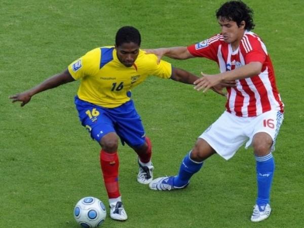 EMPATADOS. Hasta en dorsales empataron ecuatorianos y paraguayos. Valencia es retenido por Riveros (Foto: FIFA.com / AFP)