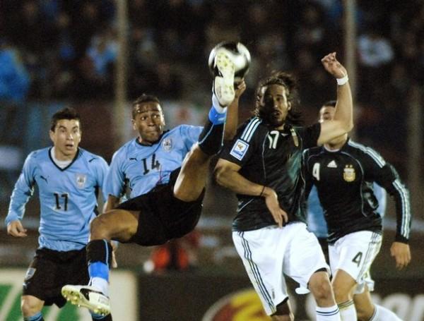 CHALACA A LA URUGUAYA. Álvaro Pereira ensaya una interesante acrobacia ante Jonás Gutiérrez. El partido se jugó al milímetro (Foto: Reuters)