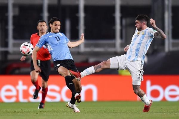 De Paul anticipa a Cavani, quien ingresó en el complemento. El volante del Atlético de Madrid marcó el segundo gol albiceleste. (Foto: AFP)